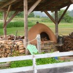 Wild Caraway's functi0oning wood-fired pizza oven with raised herb bed in foreground