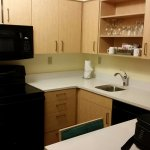 kitchen with full size appliances, coffee makings, dishes, breakfast bar with four stools
