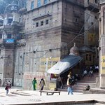 The building above the blue Yatra board is the Palace on Steps Hotels as viewed from the ghat.