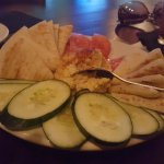 Hummus Appetizer with tomato slices, cucumber slices, and warm pita bread.