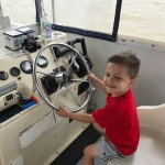 son driving the boat