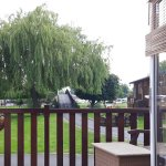 Relax in the lounge and gaze across the decking to the willow trees