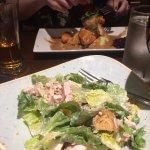 Caesar salad front, chicken in white wine sauce behind.