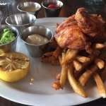 Fish and chips plate with small fish portions. Tiny peas portion in condiment cup. $24