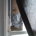 "Broken window, ""repaired"" with cardboard and duct tape."
