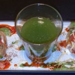 Pani puri served with a shot of cumin, coriander and lime juice