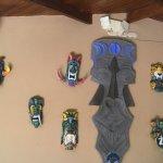 Masques tribaux exposés près du bar du restaurant, aussi planche de surf d'un artiste local.
