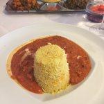 Chicken masala dish with rice - vegetarian platter in background