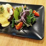 smoked salmon egg benedict with spinach on a danish. side of salad