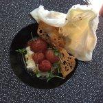 The mis-shapen white layer was a mozzarella ball! It popped and underneath were delicious tomato
