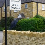 The entry is framed with a lovely Cotswold dry stone wall.