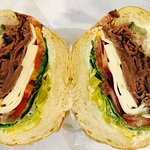 Roast beef deli sandwich with yellow peppers, red onion and Havarti