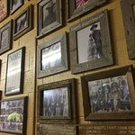 Historic photos of cowboys in wooden frames with iron brands fill the walls and complement the p