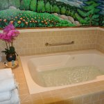 Jacuzzi tub with mural and flowers in room 39 at Lone Oak Lodge