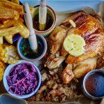 Rotisserie chicken served with stuffing, chips, ruby slaw, corn on the cob, gravy
