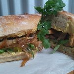 Grilled pork banger sarmie on ciabatta with dijon mustard, caramelised onions & rocket