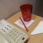 The neat & clean bedside table with a red pencil & red plastic glass