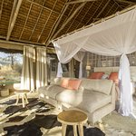 Double room with thatched roof and safari canvas sides.