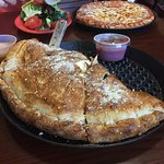 Calzone, personal sized cheese pizza and salad.