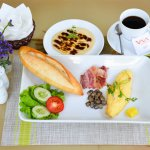 Vietnamese baguette with omelet, bacon, mushrooms. Chocolate pancake and coffee
