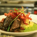 braised beef cheecks w creamy mashed, pea puree, sweet potato chips & sprouts in red wine sauce