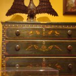 Paint decorated chest of drawers with Schimmel carved eagle on top