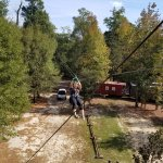Zipping over the parking area. The train cars are actually cabins for rent.