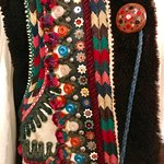 Detail of embroidery and button on man's garment