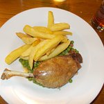 Slow cooked duck leg with green peas and chips.