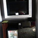 le téléviseur incorporé dans un cadre de tableau et dessous le mini-bar bien rempli