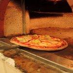 Pizza preparada con frescos ingredientes y al más puro estilo italiano, cocinada en el forno