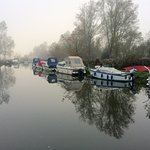 The boats on the water on a cold foggy winters morning