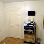 The other end of the room. The chest of drawers was the only other furniture. Door to shower roo