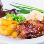 Подкопченый свиной хрящ в пикантном соусе с ароматной квашеной капустой и картофельными дольками