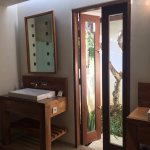 Bathroom with double vanities opened onto a small courtyard with a frangipani tree.