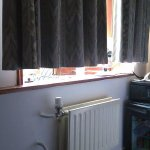 Short curtains, space between bed and window, other side is a wall. TINY room