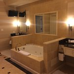 Large jetted tub with his and her sinks to the right and left with a large walk in shower