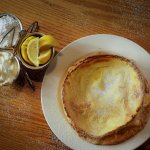 Dutch Baby with oven baked served with fresh lemons, whipped butter and powdered sugar.