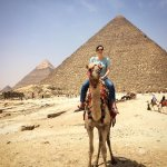 Riding a camel in front of the pyramids!