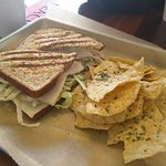 Turkey panini with salad and swiss cheese and tortilla chips