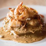 LOW COUNTRY SHRIMP & GRITS jumbo shrimp, cheddar grit cake, tasso ham, sherry cream.