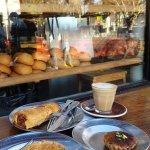 Sausage roll, bacon quiche, creme brulee tart, latte, against the shop front