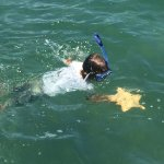My son swimming back to the boat with a starfish he found