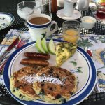 Breakfast: quiche, sausage, juice, coffee, fruit and pancakes made with wild Maine blueberries.