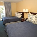 Two Queen bed, located in 2-story building overlooking pool area. Wall heater & portable fan roo