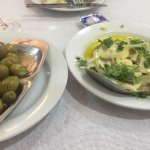 Simple starters, crushed green olives and a salad of white salad onions, garlic and sardines