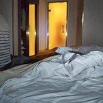 La cama desecha, y al fondo la puerta de cristal del baño