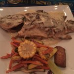 Whole grilled fish with butter sauce.