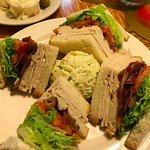 Triple decker turkey club sandwich with potato salad