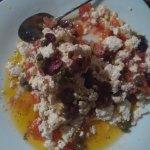 Dakos in progress (feta, fresh tomatoes, olives, and large bread crumbs)